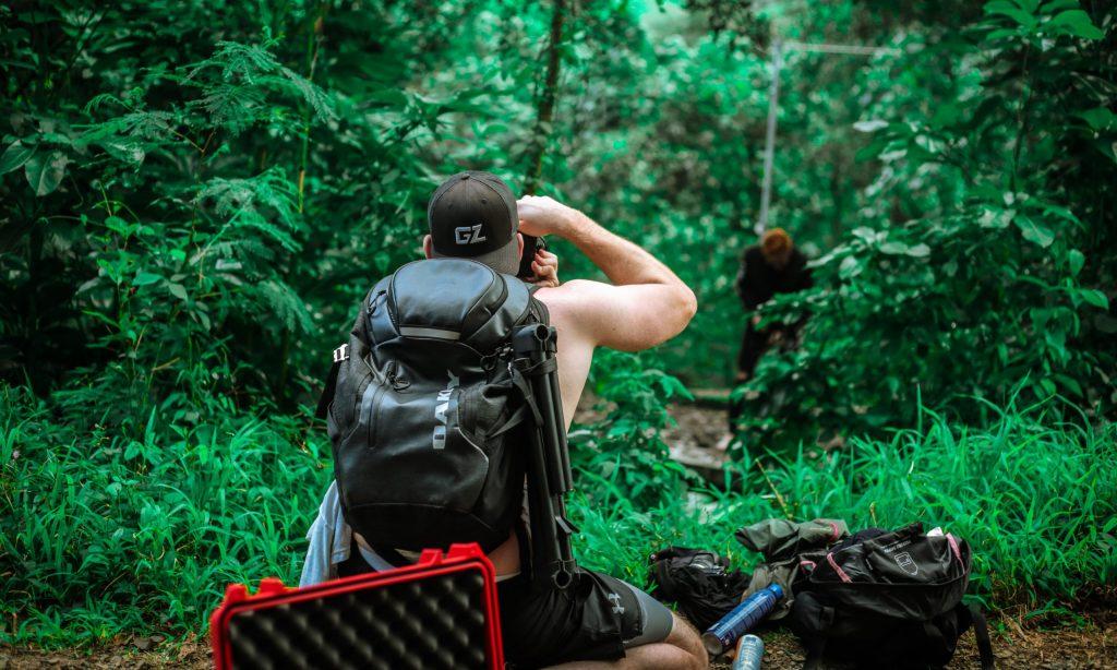 Imagem mostra um homem, de costas para a câmera, usando uma mochila da Oakley e apontando uma câmera fotográfica para um modelo, no meio de uma floresta fechada.