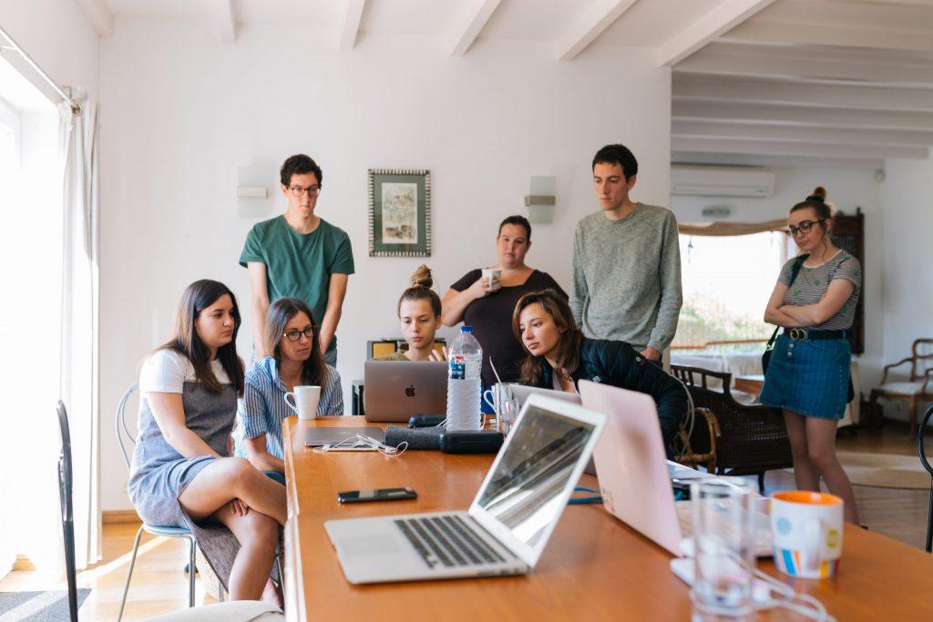 Pessoas trabalhando em volta de um notebook, em uma mesa comprida.