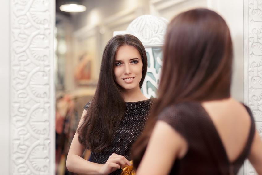 Mulher se olhando em frente ao espelho.