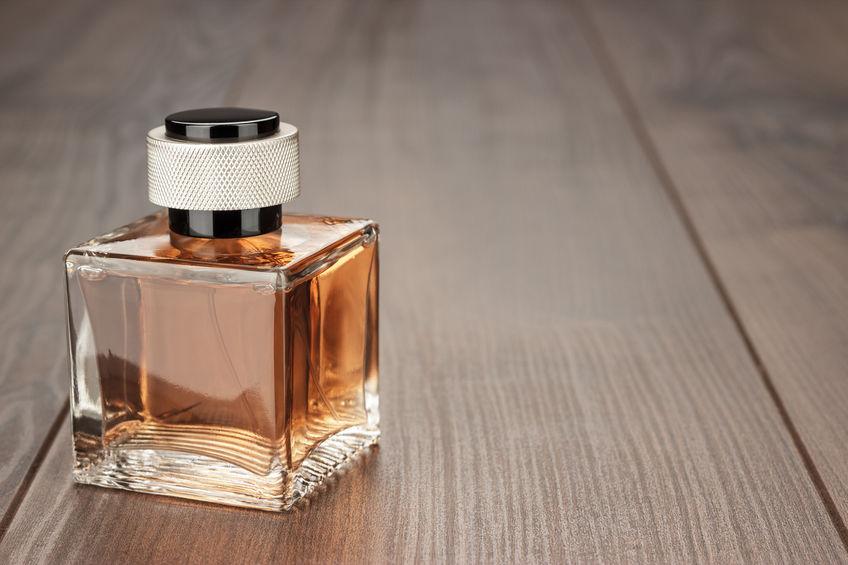 Pequeno frasco de perfume masculino sobre superfície de madeira.