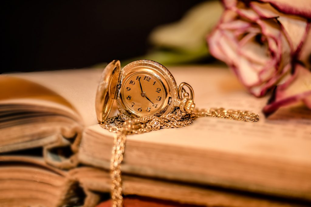 Na foto um relógio de bolso dourado em cima de um livro aberto.