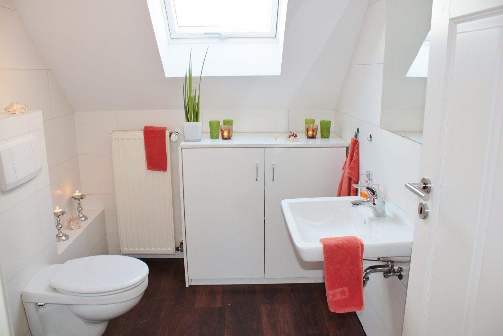 Banheiro branco com toalhas de rosto vermelhas