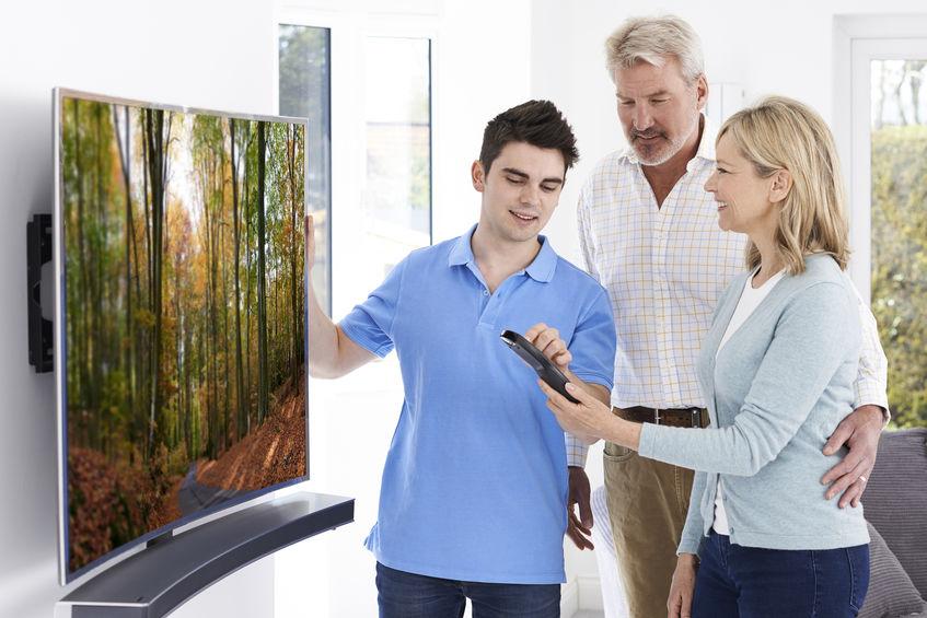 Casal aprendendo a mexer em TV com técnico.