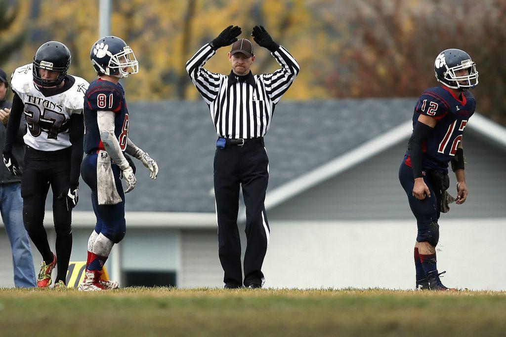 Imagem mostra, ao centro, um árbitro de futebol americano, com os braços levantados, assinalando um lance. Em sua mão esquerda, um apito esportivo com dedal. Ele tem dois jogadores à sua direita, e um à sua esquerda.