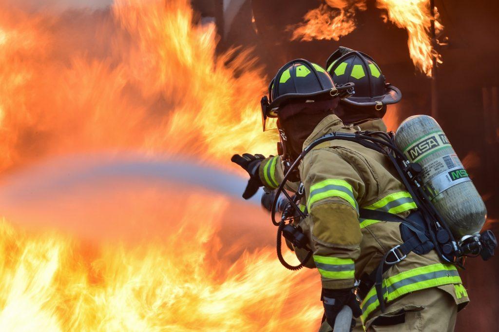 Imagem mostra dois bombeiros, usando balaclavas, combatendo uma alta chama.