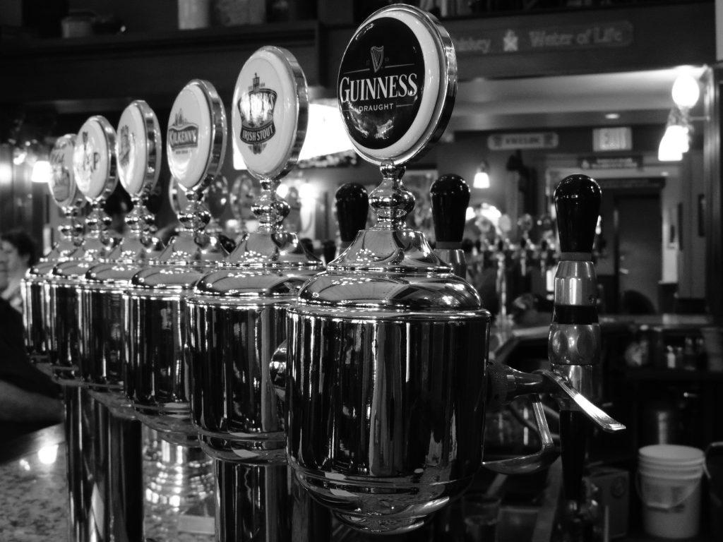 Imagem, em preto e branco, mostra seis chopeiras grandes enfileiradas no balcão de um bar.
