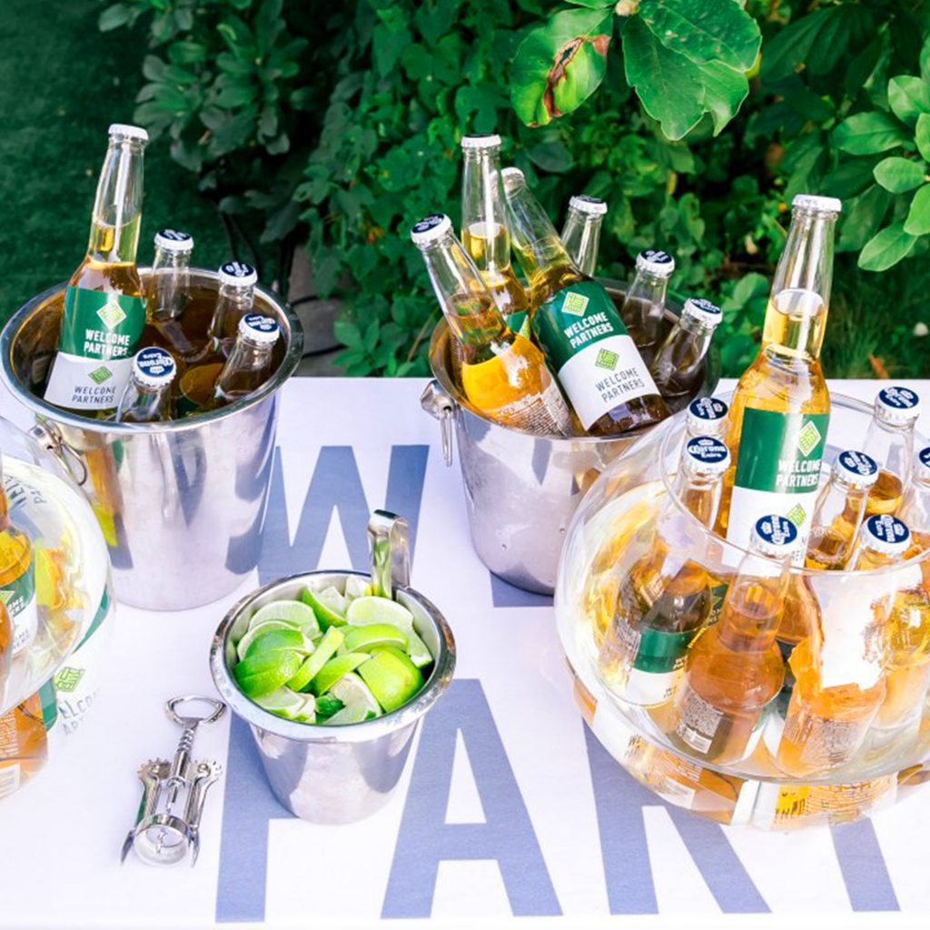 Imagem de coolers de cerveja em formato de balde recheados de cerveja sobre mesa externa