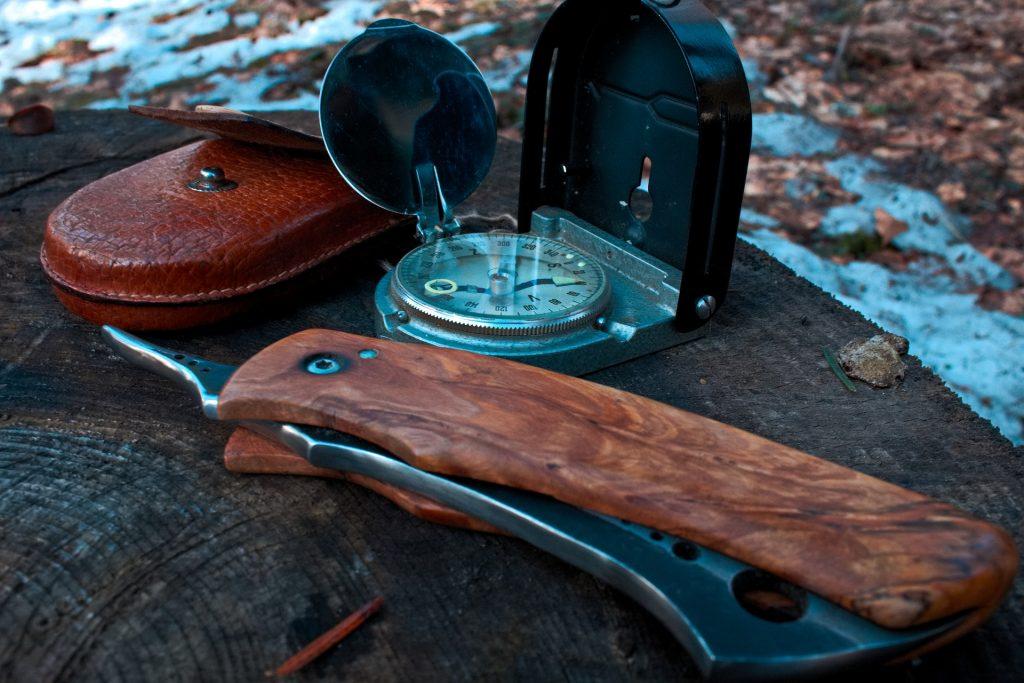 Imagem mostra em close um conjunto de itens de sobrevivência: uma faca com cabo de madeira, uma bússola de revestimento metálico e um pequeno estojo de couro. Eles tão sobre um toco de árvore.