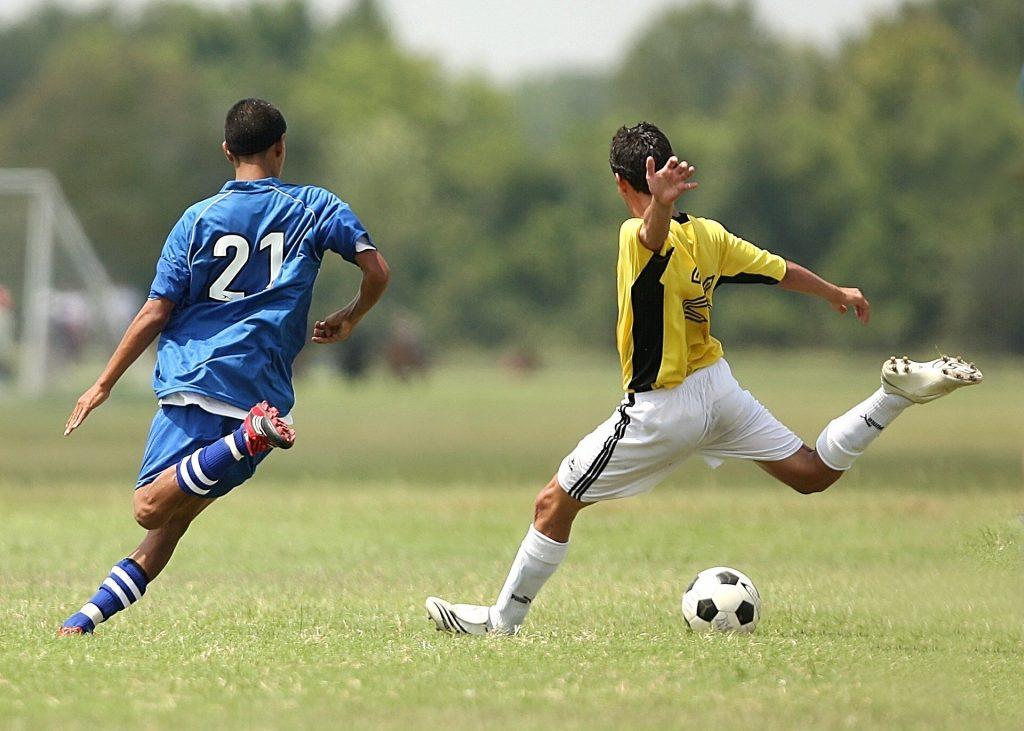 Imagem mostra dois jogadores de futebol disputando a bola.
