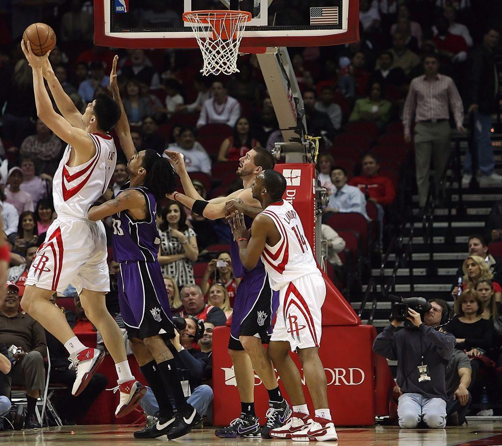 Jogadores de basquete em quadra tentando arremessar a bola na cesta.