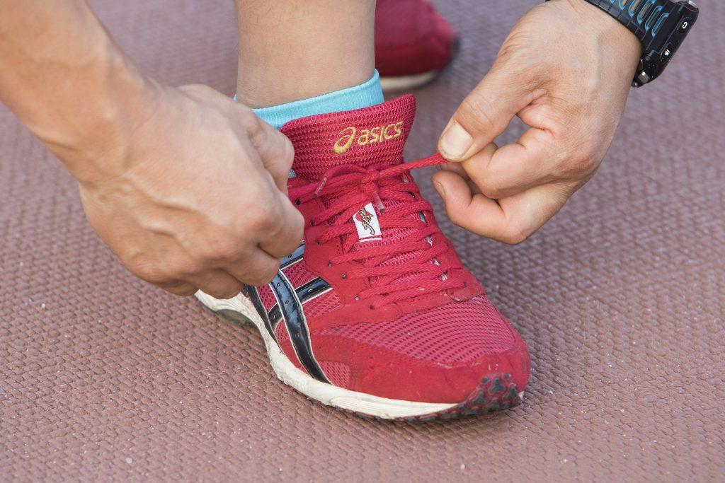 Imagem mostra uma mão amarrando um tênis de corrida, este sob um piso acolchoado.