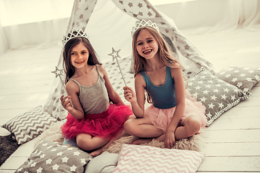 Imagem mostra duas meninas com coroas e varinhas de condão sentadas sobre um amontoado de almofadas, com uma barraca infantil ao fundo.