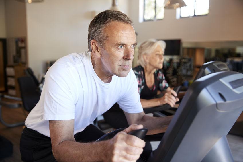 Imagem mostra um casal de idosos se exercitando dentro de casa, em bicicletas ergométricas. O home está em primeiro plano, e a mulher ao fundo, desfocada.