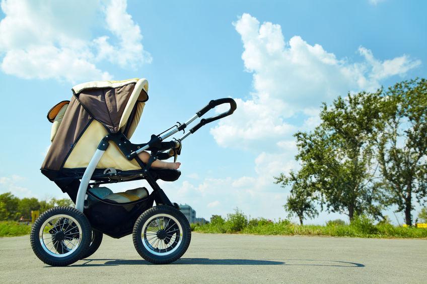 Carrinho de bebê marrom e bege em parque.