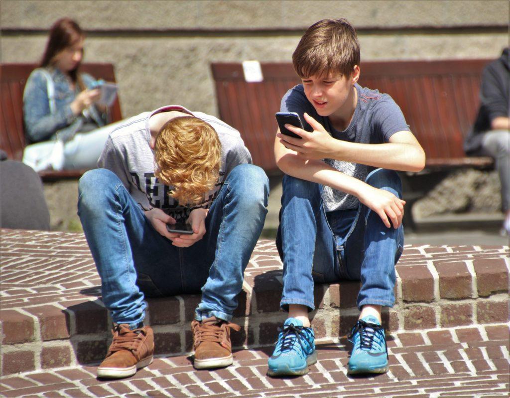 Imagem de dois garotos mexendo em seus celulares.