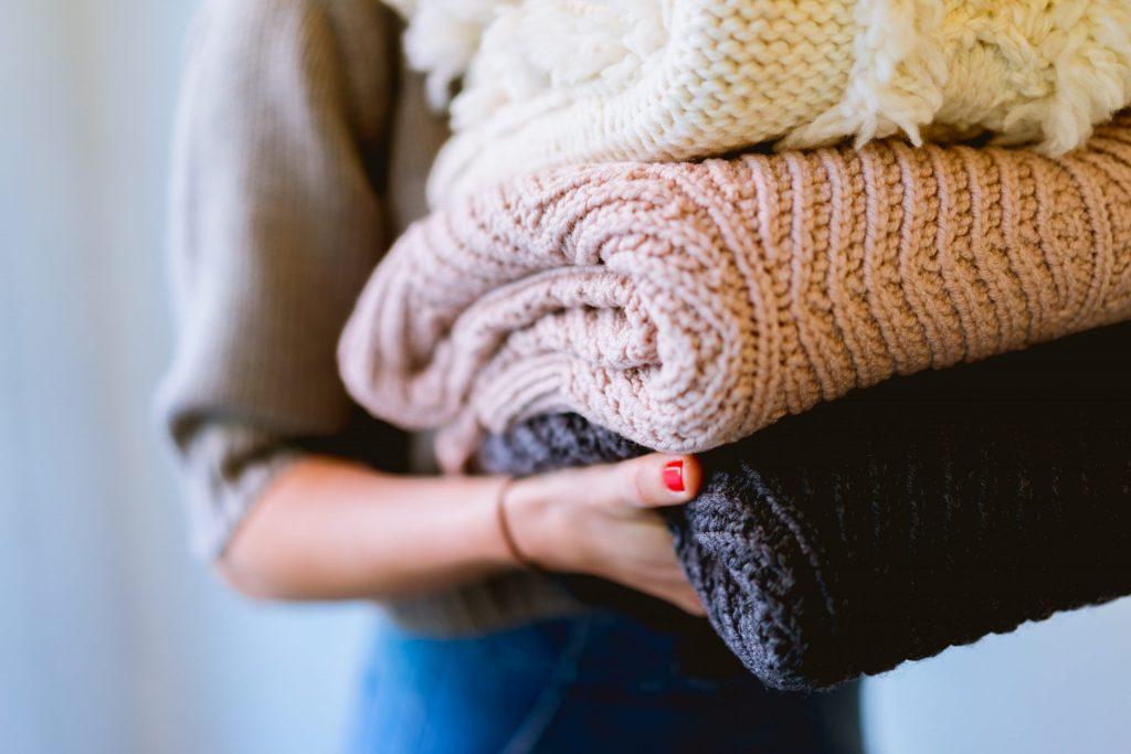 Imagem de uma mulher carregando uma muda de roupas.