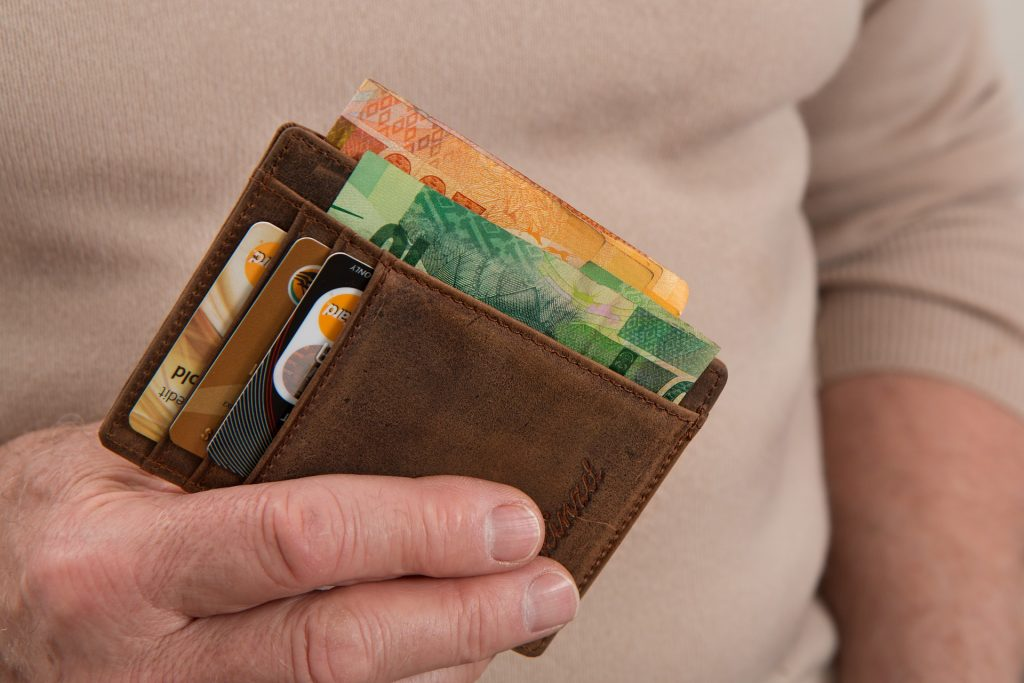 Homem segurando carteira com notas de dinheiro.