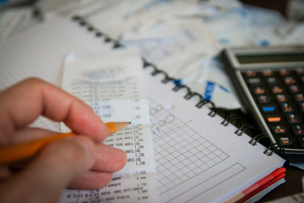 Mão segurando lápis, com notas, papéis e calculadora.