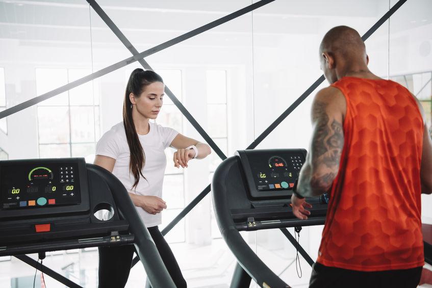 Imagem mostra um homem, de costas para a câmera, correndo em uma esteira de uma academia, orientado por sua personal trainer, que observa seu relógio de pulso.