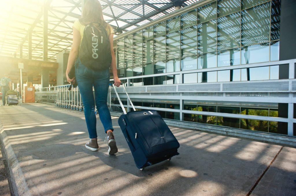 Imagem mostra uma mulher no lado de fora de um aeroporto, puxando uma mala de rodinhas e usando uma mochila Oakley.
