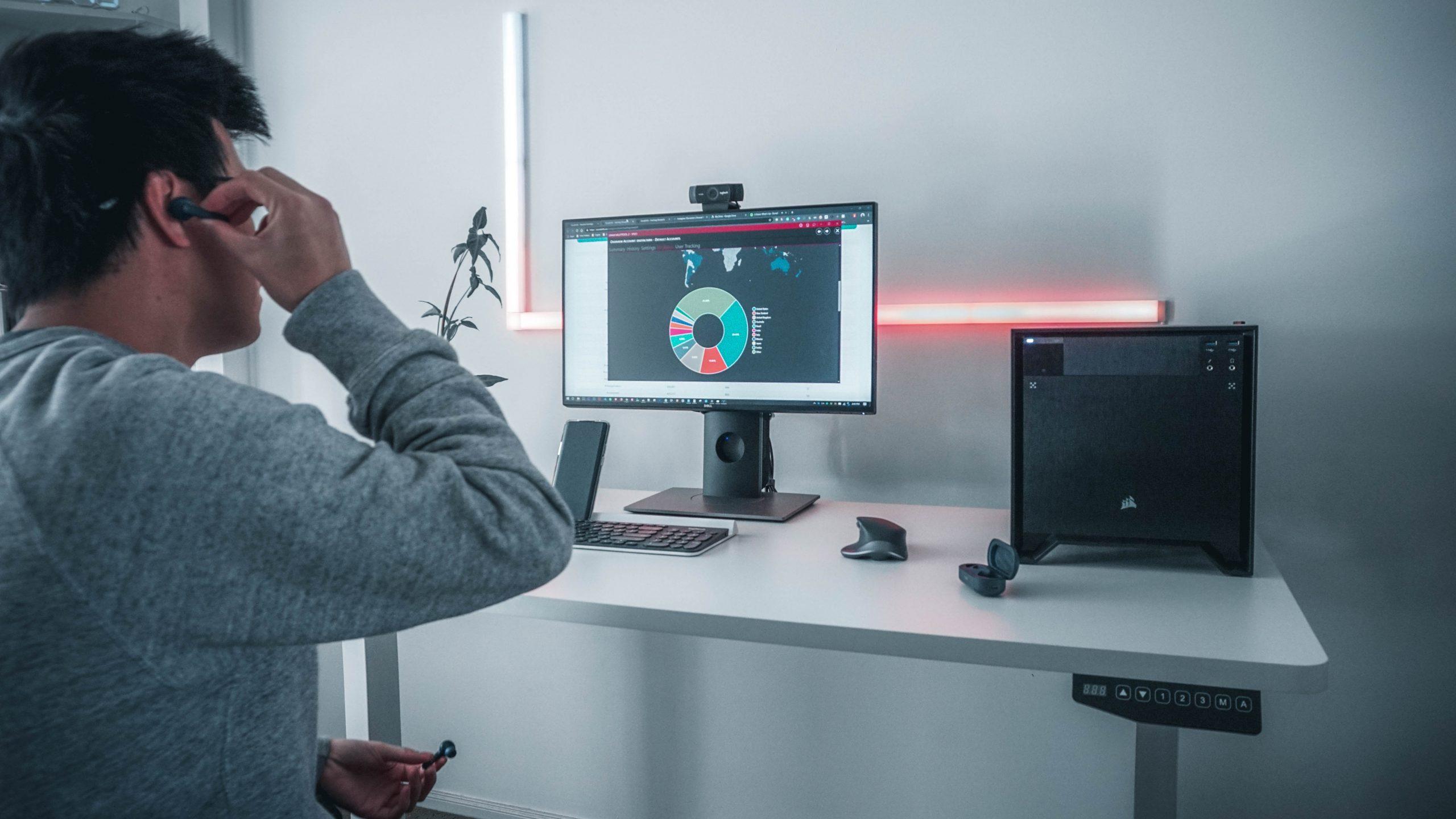 Imagem mostra um homem, sentado em frente à um escrivaninha com uma CPU e um monitor, colocando na orelha fones de ouvido sem fio.