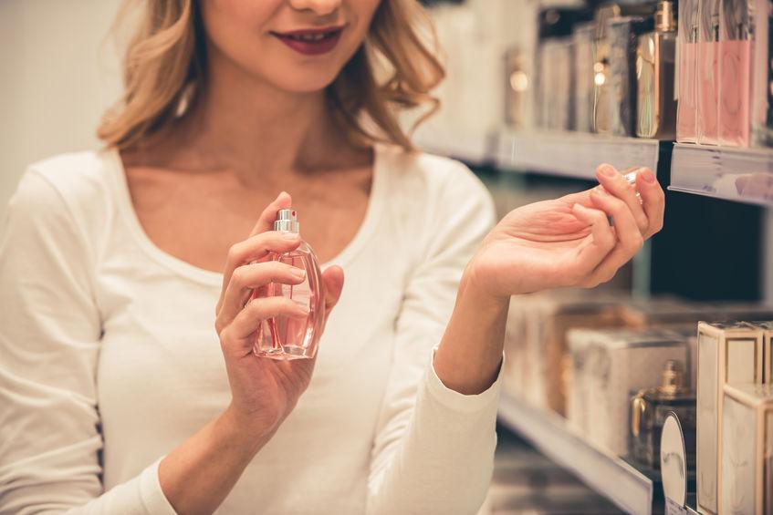 Close de mulher aplicando perfume no punho perto de prateleira cheia de perfumes.