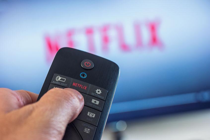 Mão segurando controle remoto com botão Netflix com tv distorcida ao fundo.