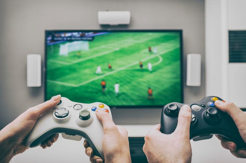 Mãos jogando videogame com controle sem fio.