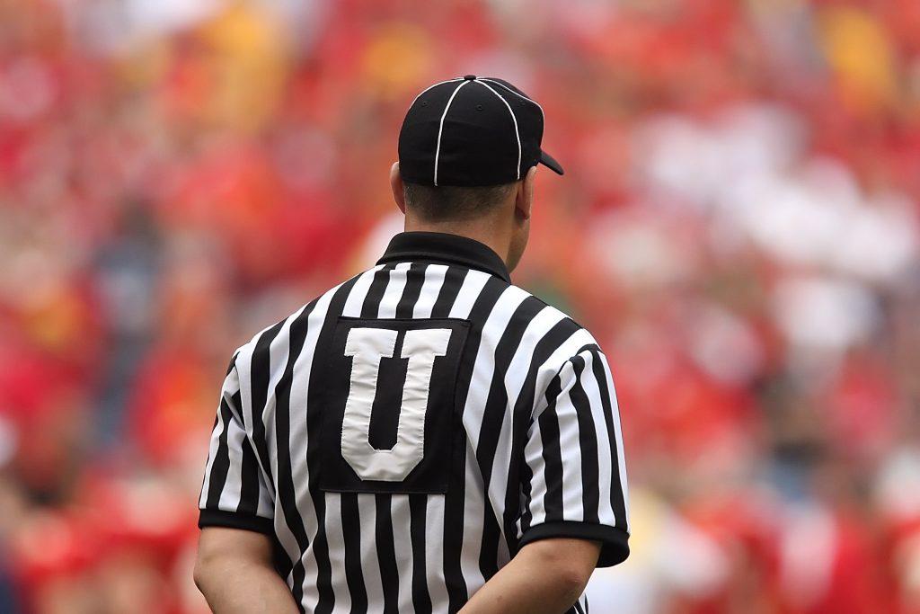 Imagem mostra um árbitro de futebol americano de costas, com a torcida, desfocada, ao fundo.