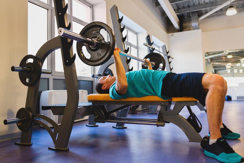 Imagem mostra um homem, deitado no banco supino de um academia, levantando uma barra com uma anilha de quinze quilos de cada lado.
