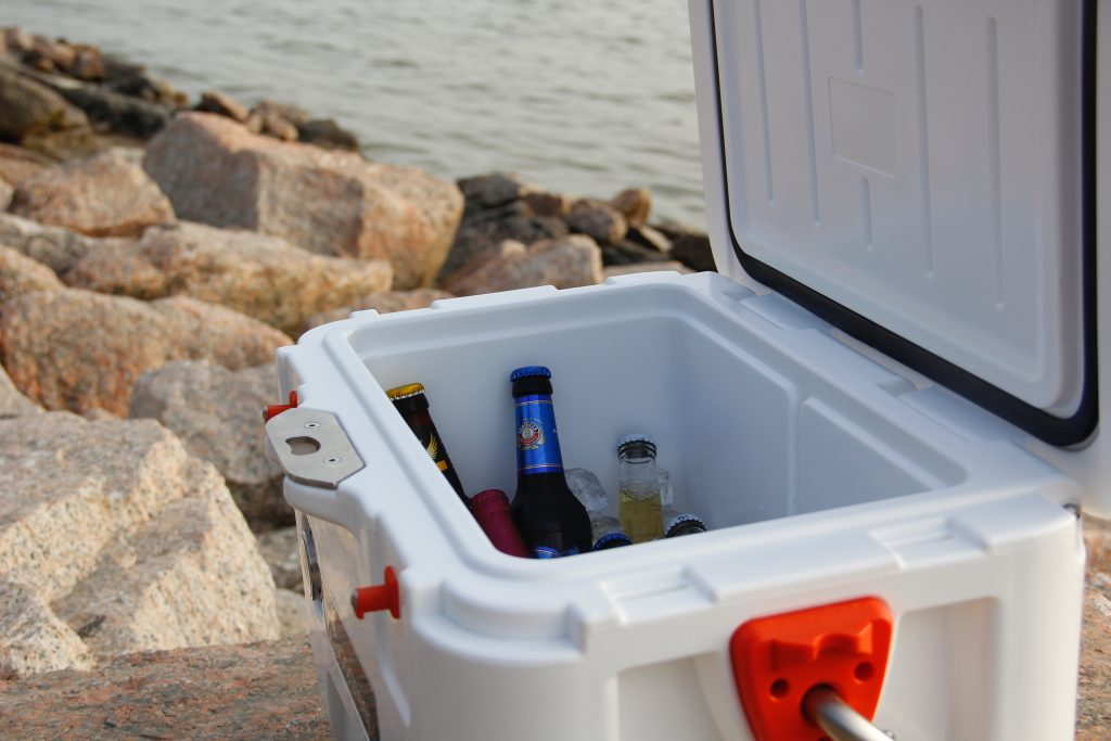 Imagem de cooler branco aberto com o interior forrado de gelo e cervejas com praia ao fundo