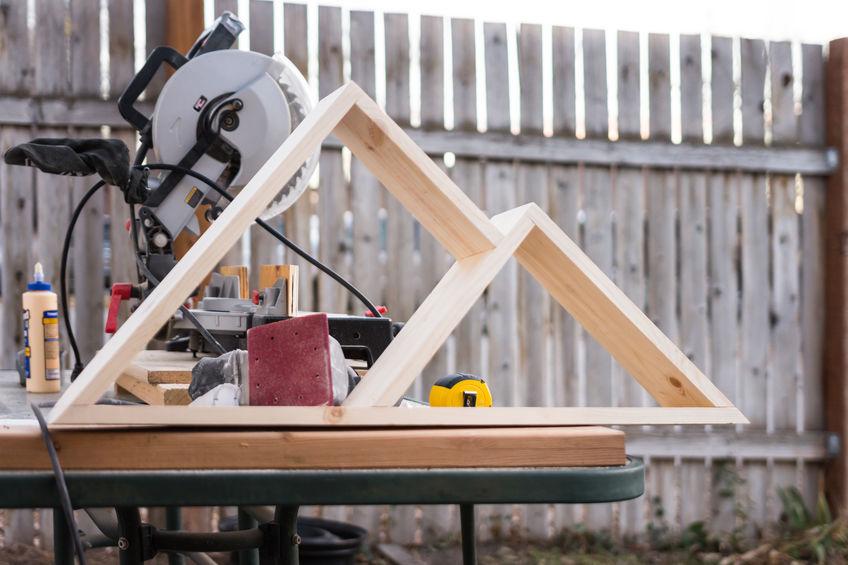 uma bancada de trabalho com algumas ferramentas e dois triangulos de madeira.