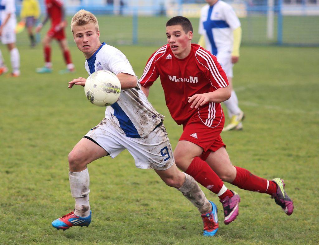 Imagem mostra dois adversários disputando a bola durante um jogo de futebol. O jogador da esquerda, de branco, tem os meiões completamente manchados com lama.