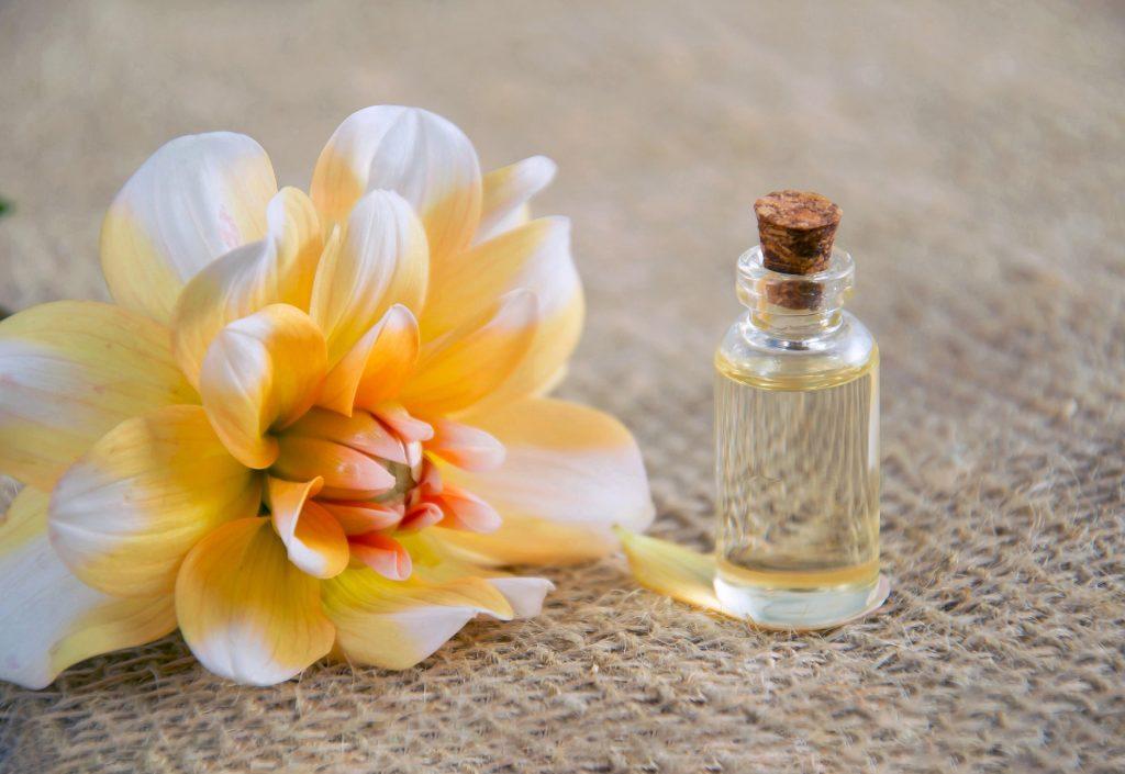 Imagem de um frasco pequeno com óleo ao lado de uma flor alaranjada.