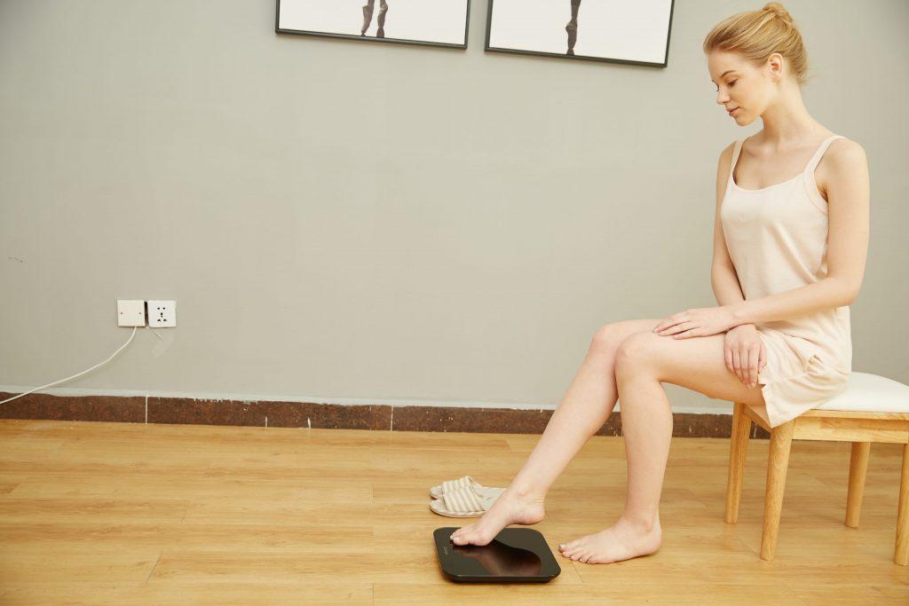 Imagem de uma mulher colocando os pés na balança.