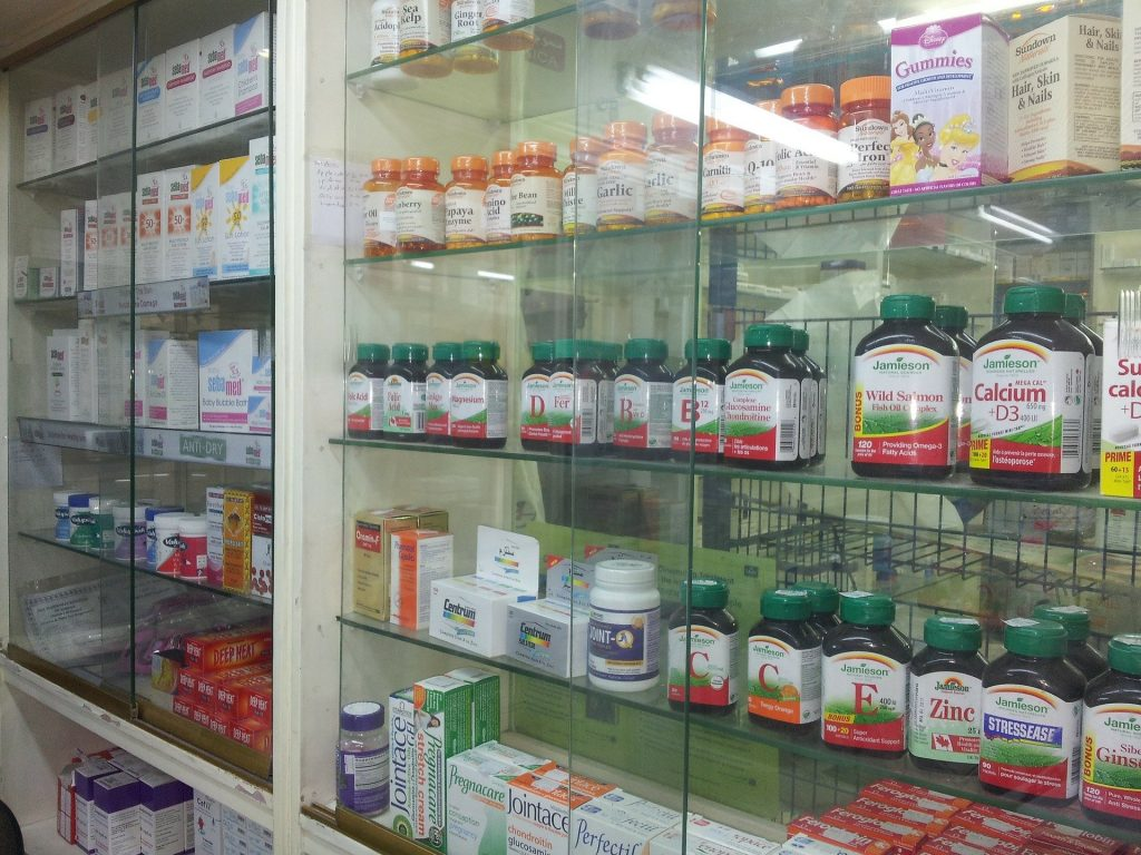 Prateleira de farmácia com vários potes de suplementos.