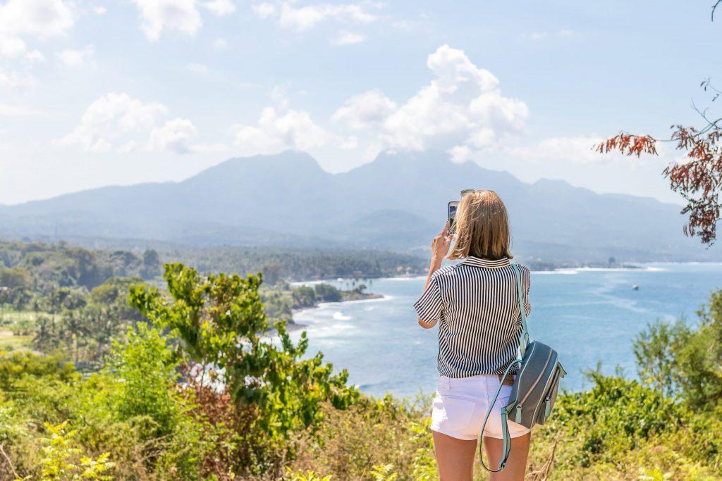 Imagem de uma mulher tirando uma foto de uma praia.