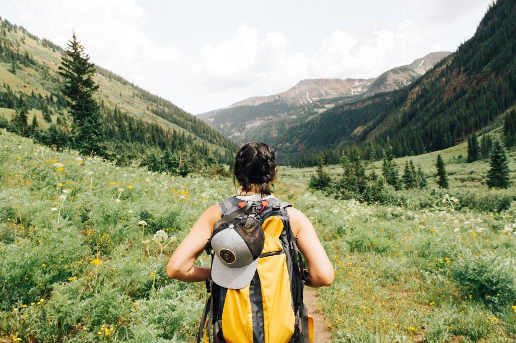 Imagem mostra uma mulher, de costas para a câmera, caminhando por um campo aberto, com montanhas ao fundo. Ela usa uma mochila cargueira com um boné pendurado no seu topo.