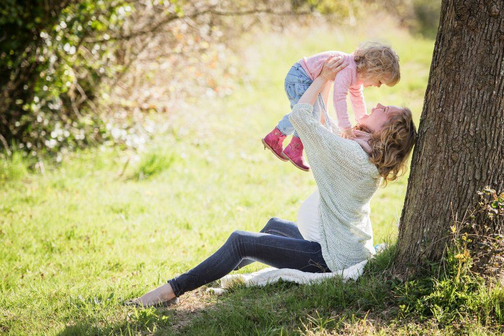 Mulher grávida, sentada na grama, debaixo de uma árvore, carregando criança.