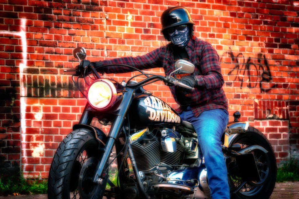 Imagem mostra um motoqueiro com uma balaclava de caveira, posando para a foto montado na sua moto.