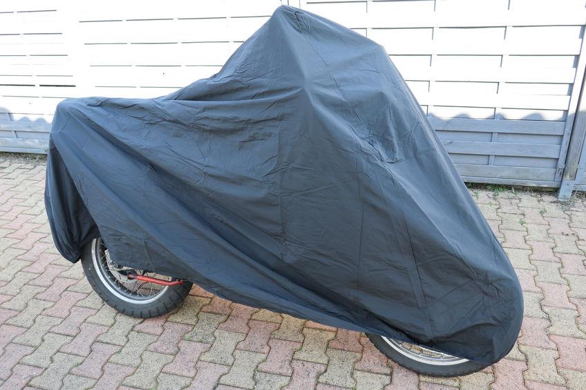 Imagem de uma moto coberta por uma capa