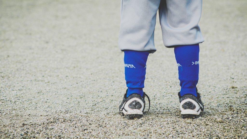 Imagem mostra um close das panturrilhas de uma criança. Ela usa uma calça curta, e seus meiões são visíveis, logo acima de seu calçado. Ela está sob um terreno de cascalhos