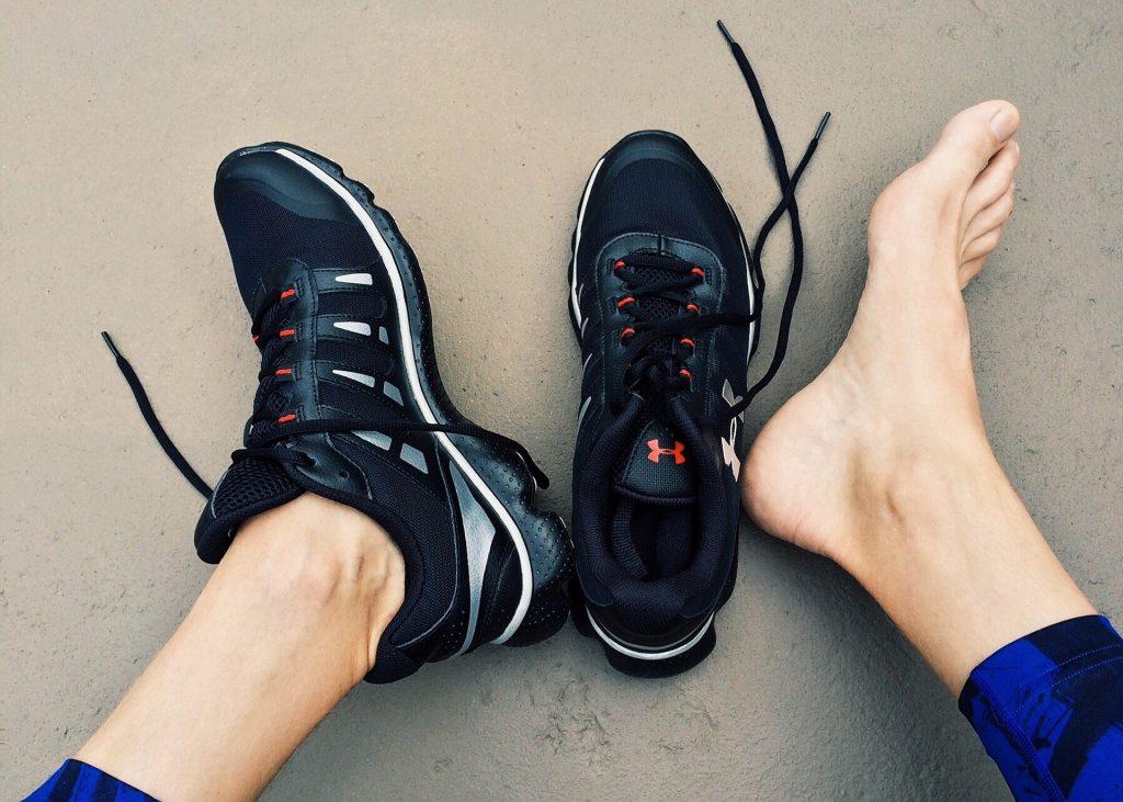 Imagem mostra dois pés e um par de tênis de corrida. O pé esquerdo está calçado, enquanto o direito repousa ao lado do seu correspondente do par.