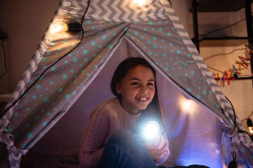 Imagem mostra uma menina sentada sob uma barraca infantil, montada dentro do seu quarto. Ela ri, enquanto segura uma lanterna acesa.