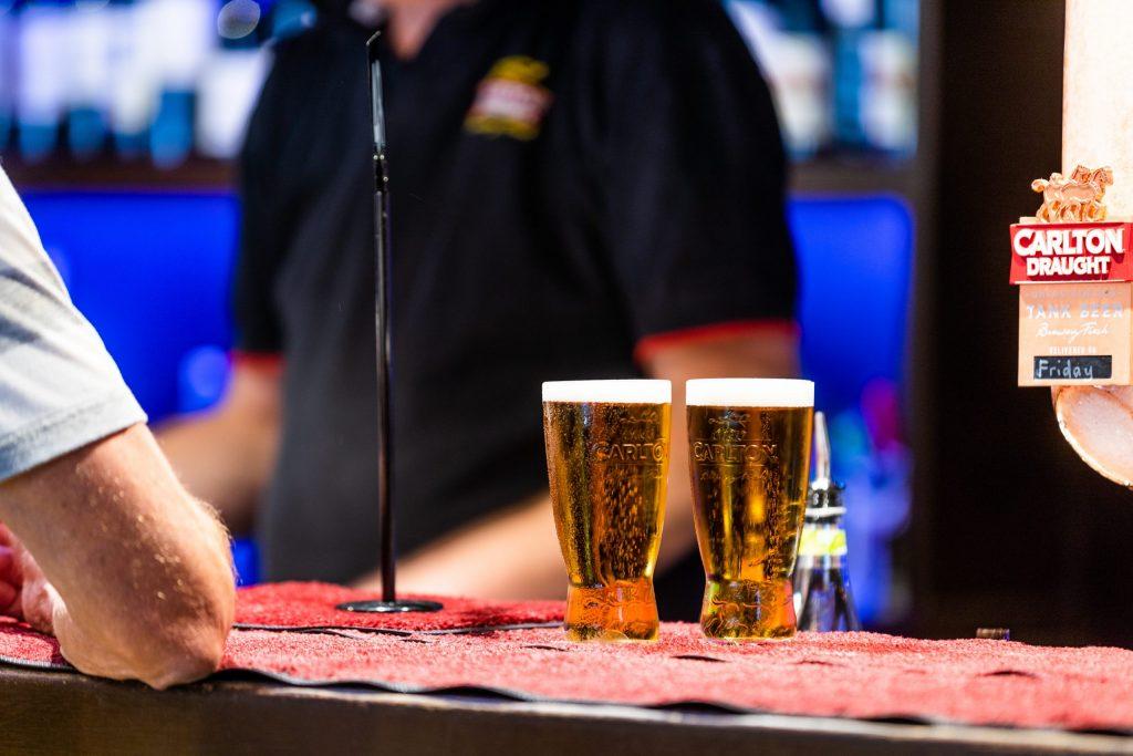 Imagem mostra dois chopps recém-tirados, repousando no balcão de um bar. Ao seu lado, uma pessoa, que sai do quadro, tem o cotovelo apoiado no mesmo balcão.