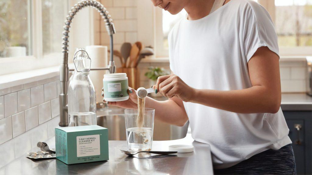 Imagem de uma mulher preparando um shake.