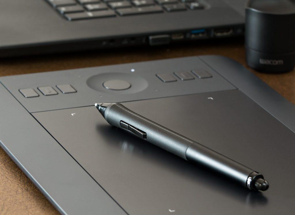 Imagem de uma mesa digitalizadora e caneta digital Wacom.