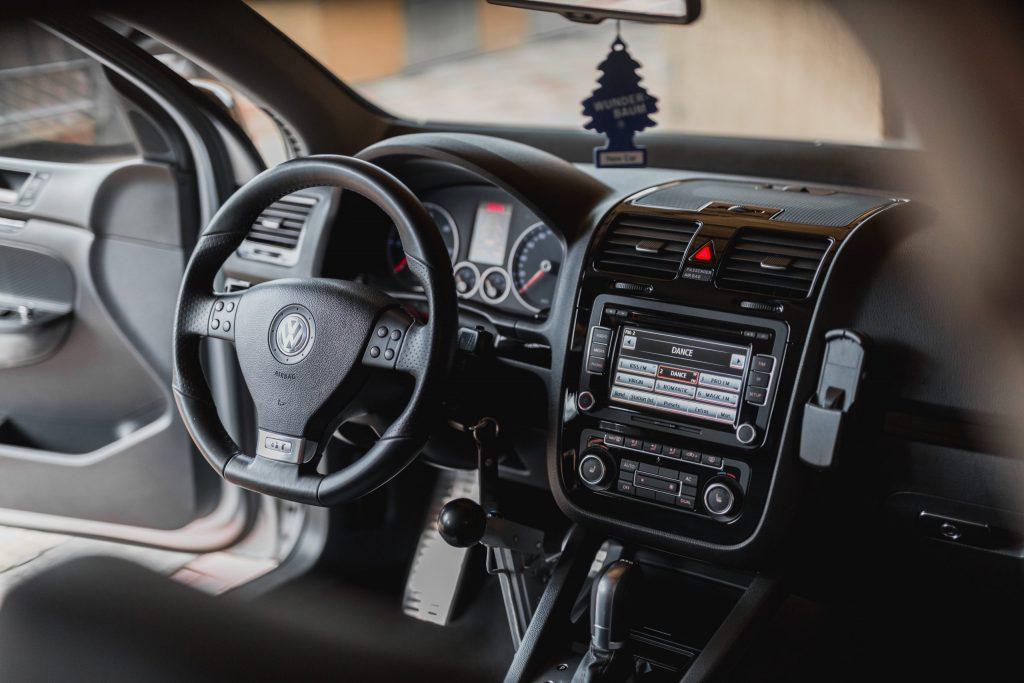 Imagem mostra o interior de carro, com os bancos vazios e a porta do motorista aberta, com o sistema de som ligado.