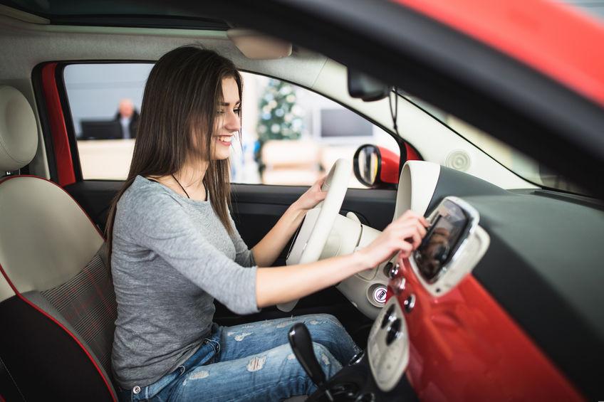 Mulher sentada dentro de um carro vermelho mexendo no som automotivo