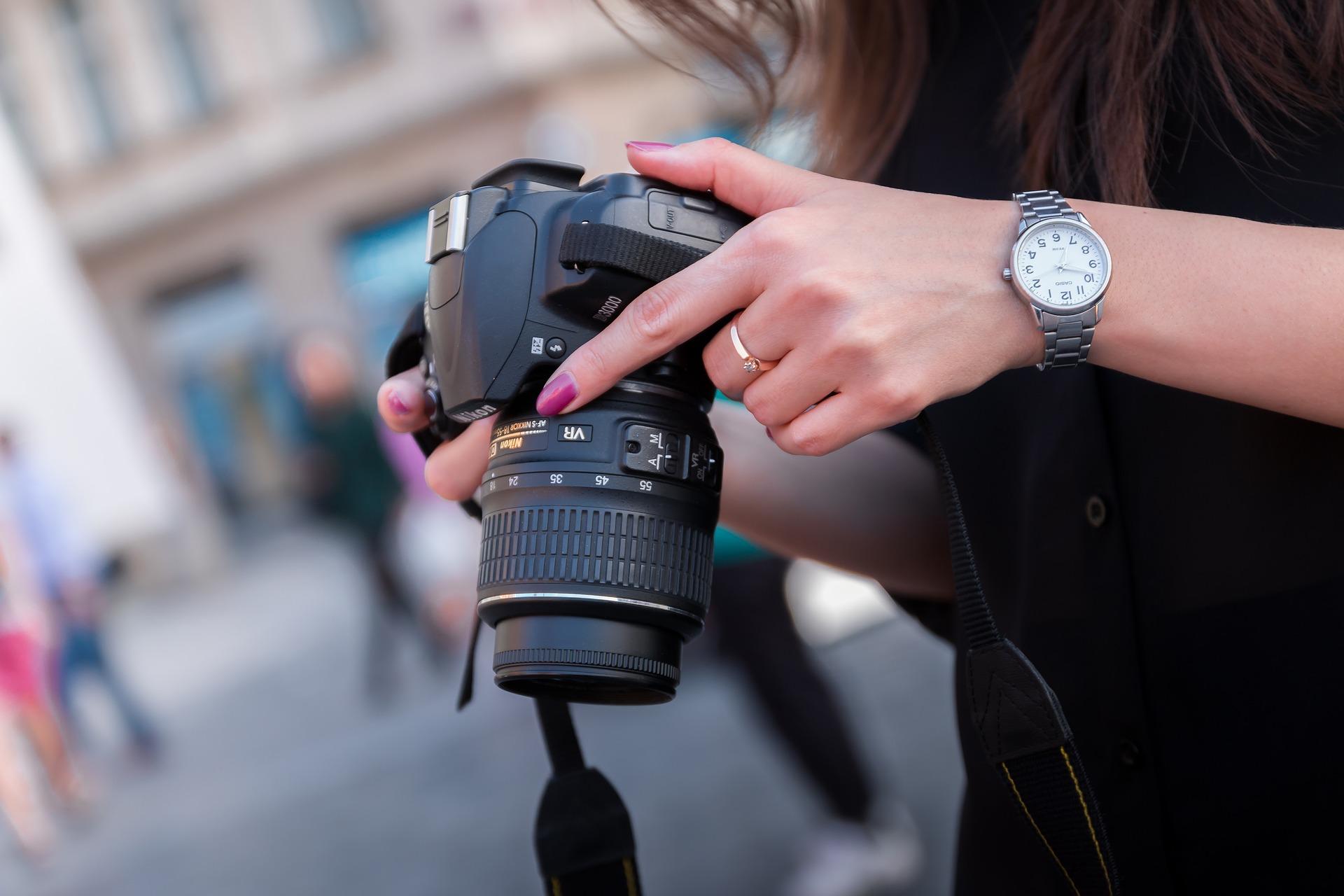 Imagem de uma mulher ajustando sua câmera.